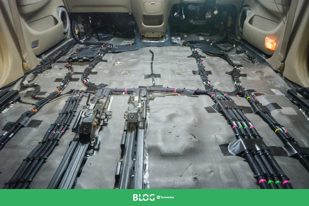 Assoalho de um automóvel com vários cabos organizados com malhas expansíveis